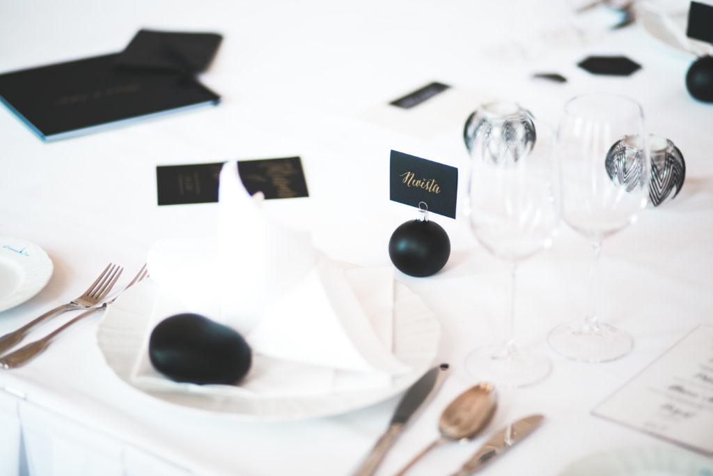 Stavební stolování s černými dekoracemi. Černé jmenovky a svícny.