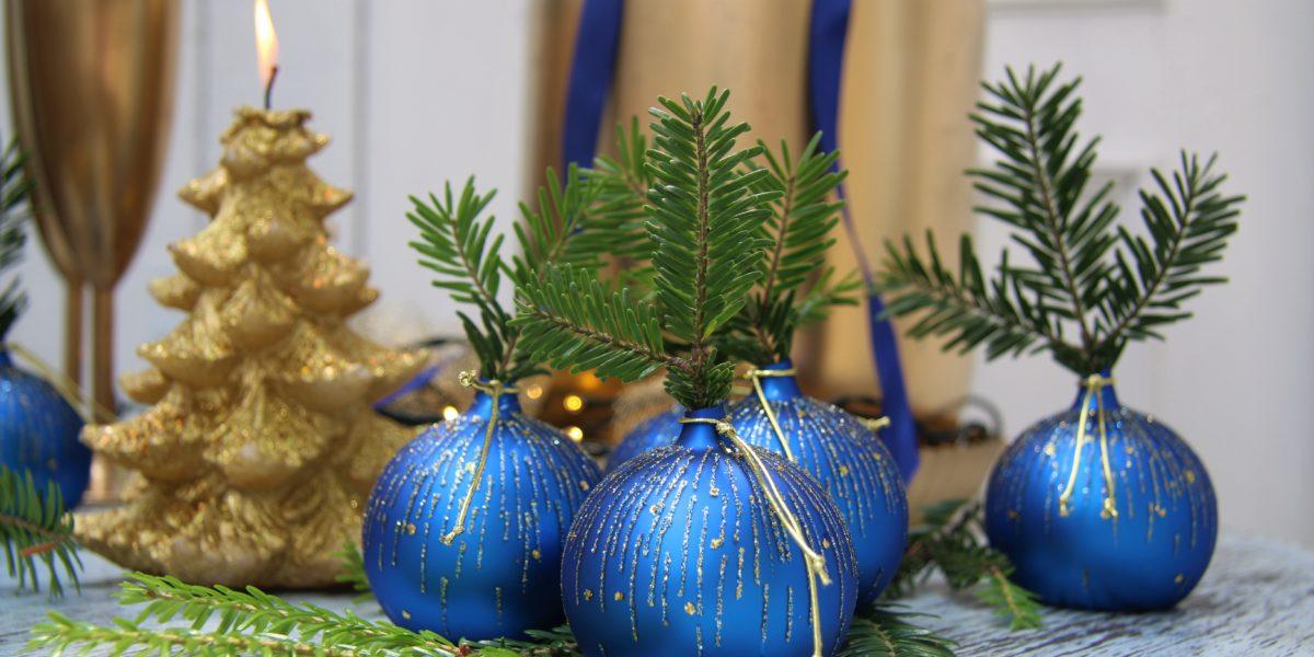 Vánoční ozdoby jako skleněné vázy na jehličí.